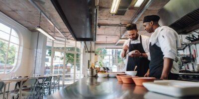 Zwei Köche stehen in einer Gastronomie-Küche und bereiten Mahlzeiten zu.