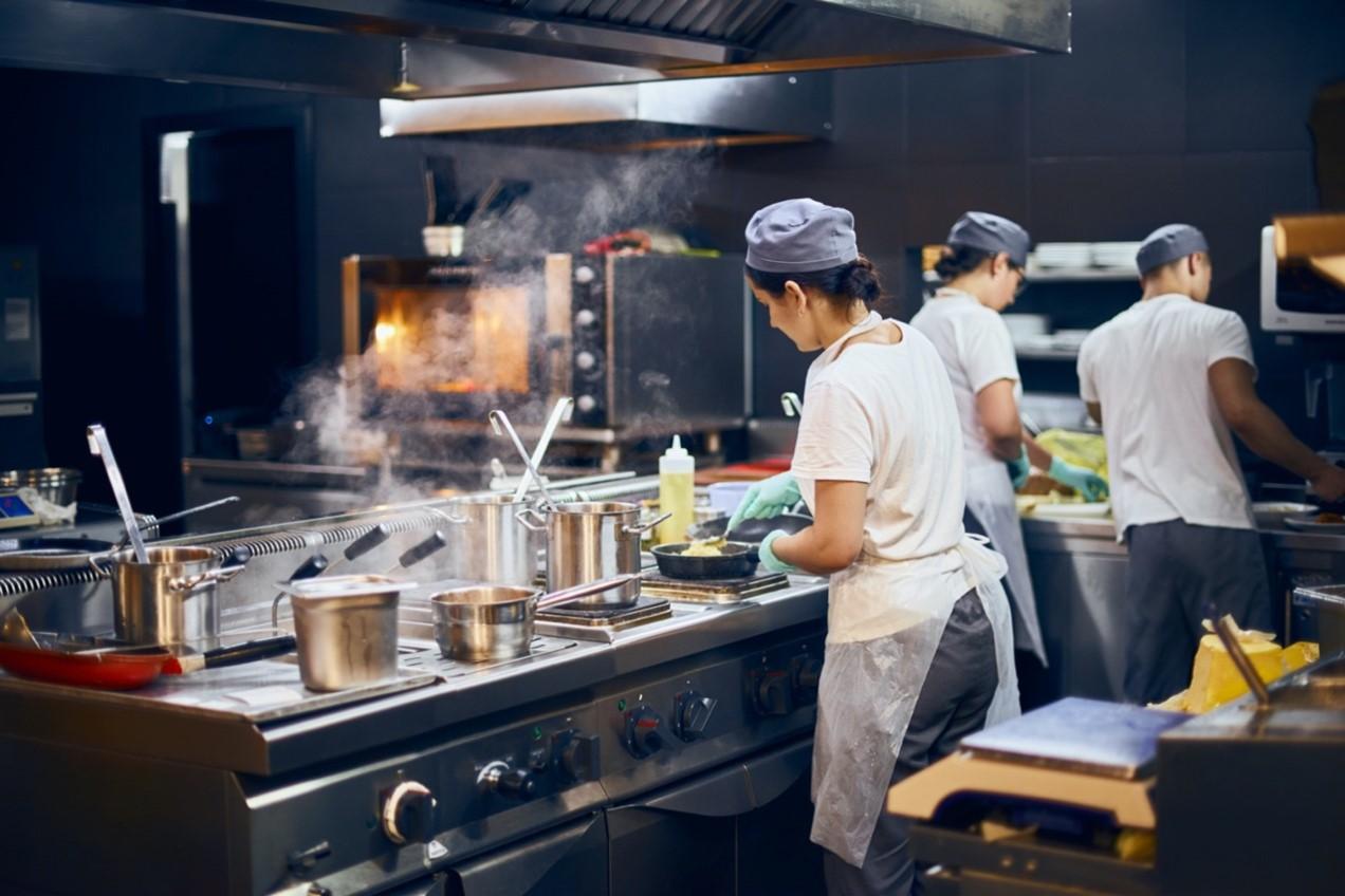 Ein Team von Köchen beim Workflow in einer modernen Gastro-Küche.
