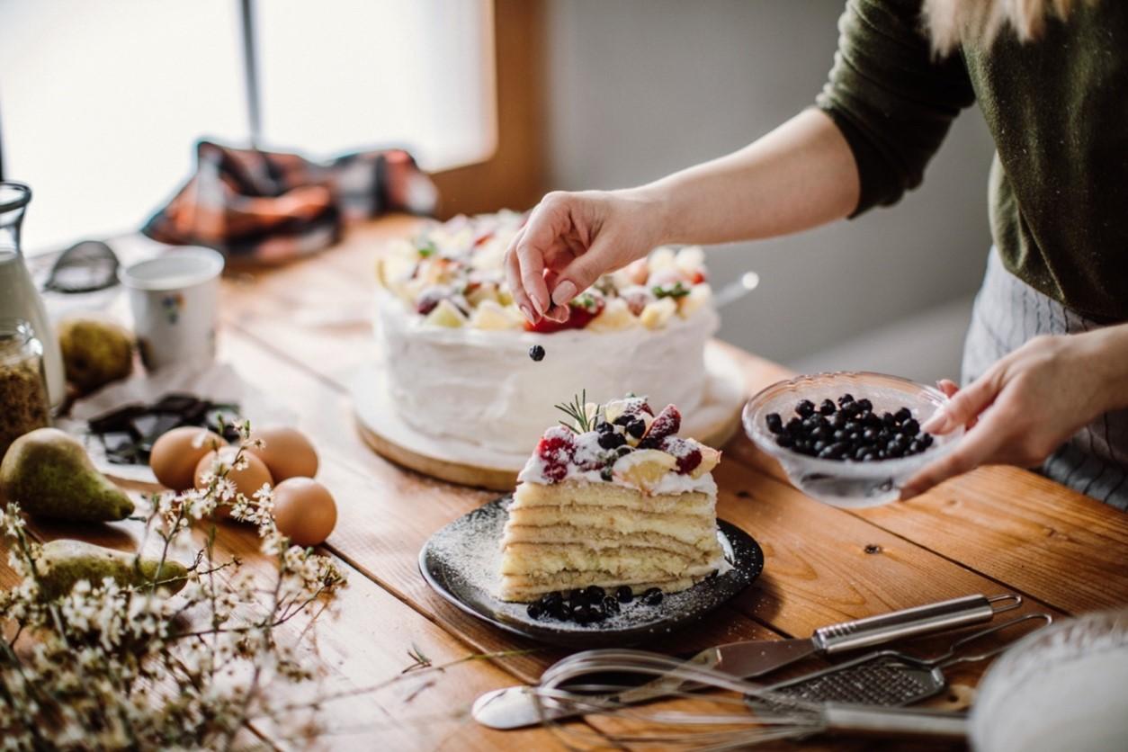 Frau garniert eine Torte mit frischen Beeren.