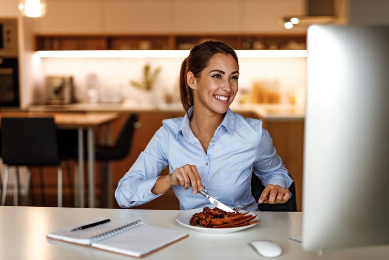 Junge Frau sitzt lächelnd vor ihrem Computer und isst zu Mittag.